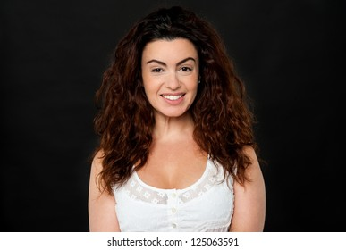 Profile shot of a gorgeous woman with lustrous hair on black background.