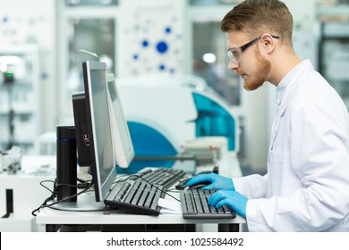 Profile shot of a handsome bearded male young professional scientist working on a computer at the modern laboratory copyspace technology medicine chemistry biology connection researcher.