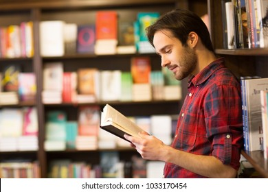 Profile shot of a handsome young man reading a book at the library or bookstore leaning on the shelf copyspace interesting lifestyle hobby education learning studying project information youth.