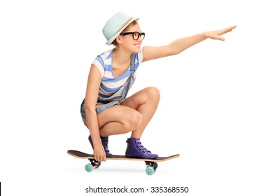 Profile shot of a hipster girl riding a skateboard and pointing forward with her hand isolated on white background