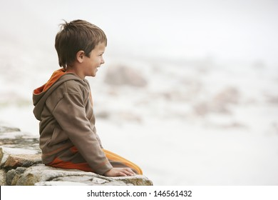 Profile shot of little boy sitting on wall at beach