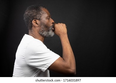 Profile shot of a man in white t-shirt covering his mouth with hand while coughing