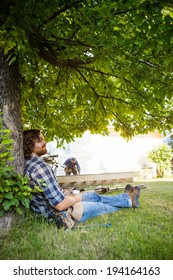 Profile shot of manual worker with eyes closed leaning on tree trunk while coworker working in background