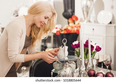 Profile shot of a mature beautiful happy woman smiling holding silver decorative pears while shopping at the home decor department at the shopping mall consumerism positivity lifestyle sales.