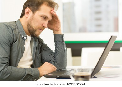 Profile shot of a mature handsome bearded businessman looking upset and tired stressing out working on his laptop at the office copyspace profession job career crisis deadlines overworking nervous