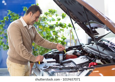 Profile shot of a mature man looking under the hood of a new car at the dealership examining engine before buying an auto automotive hobby power horsepower driving transport vehicle consumerism.