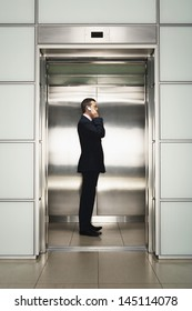 Profile shot of middle aged businessman using cellphone in elevator