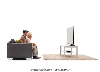 Profile shot of a senior man and woman sitting on a sofa and watching tv isolated on white background