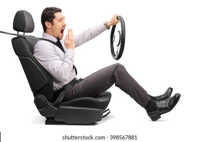 Profile shot of a sleepy young guy holding a steering wheel seated on a car seat isolated on white background