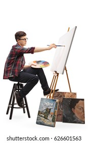 Profile shot of a teenage painter painting on a canvas with a paintbrush isolated on white background