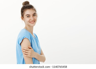Profile shot of tender and feminine beautiful female with bun hairstyle standing in profile and gently touching arm, smiling with cute expression at camera, being sensual and flirty