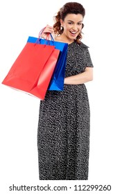 Profile shot of woman holding shopping bags isolated on white