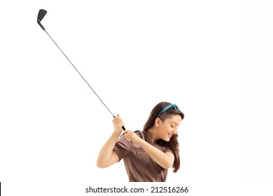 Profile shot of a woman swinging a golf club isolated on white background