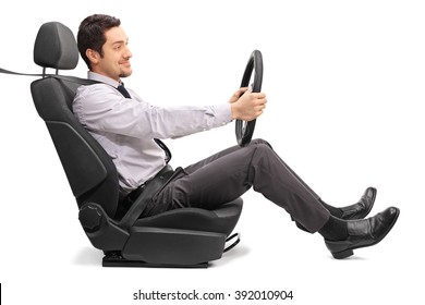 Profile shot of a young man holding a steering wheel seated on a car seat isolated on white background