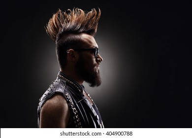 Profile shot of a young punk rocker with a Mohawk hairstyle on dark background