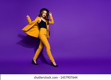 Profile side full length body size view of nice-looking gorgeous attractive content cheerful cheery wavy-haired lady motion touching hat isolated over bright vivid shine violet lilac background