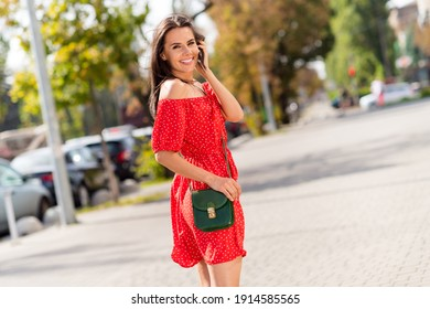 Profile side photo of adorable sweet young woman dressed red off-shoulders dress bag outdoors street city urban
