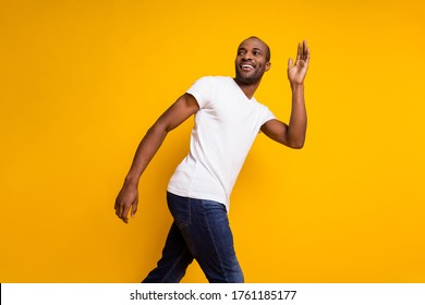 Profile side photo of charming cheerful candid afro american guy go spring walk wave hand say good bye wear trendy clothes isolated over shine color background