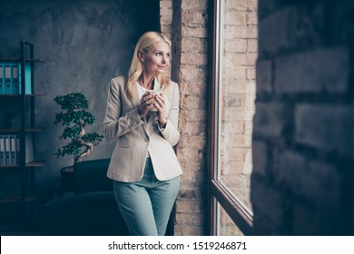 Profile side photo of dreamy peaceful middle aged woman freelancer have break hold mug with espresso look window think about future briefings with partners seminars workshop stand in workplace