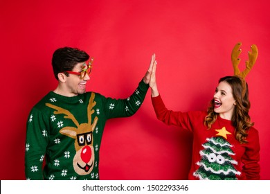 Profile side photo of funny two people family wife husband with brown hair give high five enjoy theme party wear comfort christmas tree design sweater isolated over red color background