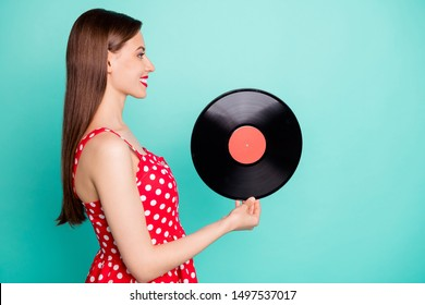 Profile side photo of lovely girl holding gramophone disc wearing polka dot dress skirt isolated over teal turquoise background