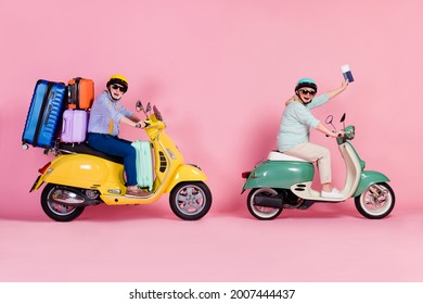 Profile side photo of senior husband wife driving motorbike helmets holding passport luggage isolated pink color background