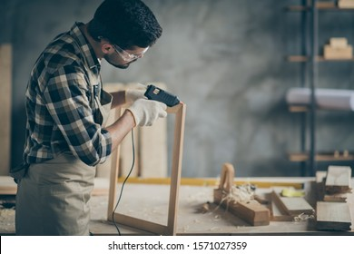Profile side photo of serious concentrated worker man use electric hot glue gun to repair wooden construction frame work in home house garage