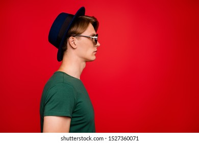 Profile side photo of serious stunning man look at copyspace listen his friends try solve difficult question like real professional expert wear casual style outfit isolated red color background
