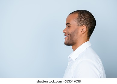 Profile side photo of smiling mulatto american business guy standing in white formal outfit on pure blue background near the copy space