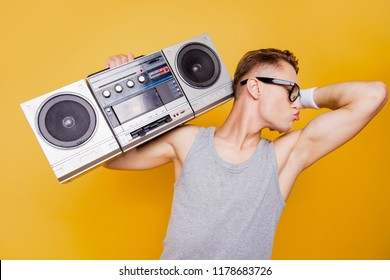 Profile side portrait of funky cheerful nice positive guy in glasses, holding, carrying boombox on shoulder, kissing hiw own biceps, fooling, isolated over bright vivid yellow background