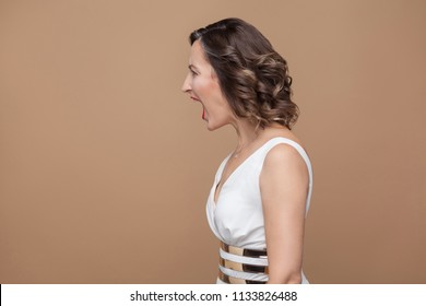 Profile side view of angry middle aged boss woman. Emotional expressing woman in white dress, red lips and dark curly hairstyle. Studio shot, indoor, isolated on beige or light brown background