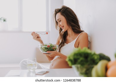 Profile side view of beautiful mama tasting salad while sitting on chair in bright light kitchen inside cozy flat