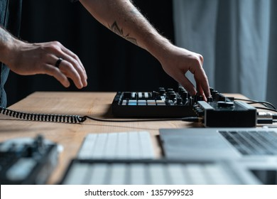 Profile side view and close-up, cropped photo tattoo hands of disc jockey master. Man using mix controller for creative music in sound recording studio