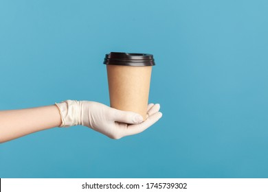 Profile side view closeup of human hand in white surgical gloves holding and showing cup of hot takeaway mug drink in hand. indoor, studio shot, isolated on blue background.