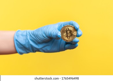 Profile side view closeup of human hand in blue surgical gloves holding and showing bitcoin symbol in hand. indoor, studio shot, isolated on yellow background.