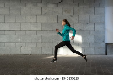 Profile side view of confident young adult athlete woman in sportswear and sneakers shoes running fast outdoor in city. Sportswoman making cardio training, moving near wall with copy space