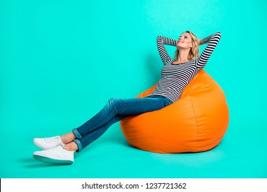 Profile side view full length body size nice pretty charming attractive cheerful wavy-haired girl in striped pullover jeans denim sitting resting after work day isolated on shine turquoise background