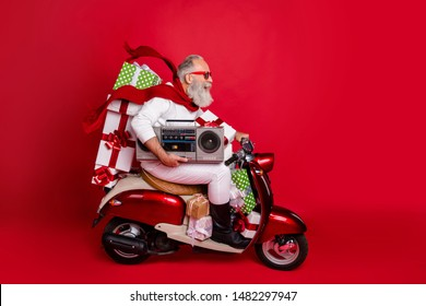 Profile side view of his he nice attractive cheerful cheery funky bearded gray-haired man carrying cool desirable purchase things eve noel celebration isolated on bright vivid shine red background