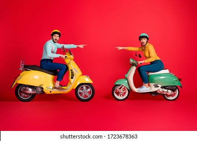Profile side view of his he her she nice attractive funny outraged couple riding moped pointing at each other blaming isolated over bright vivid shine vibrant red color background