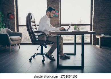 Profile side view of his he nice attractive chic confident focused man qualified IT expert economist sitting in chair preparing report at modern loft brick industrial style interior workplace station
