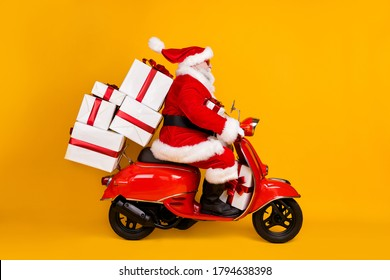 Profile side view of his he nice funny fat St Nicholas driving motor bike hurry up delivering pile stack gifts Eve Noel winter tradition isolated bright vivid shine vibrant yellow color background