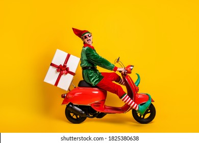 Profile side view of his he nice attractive cheerful cheery crazy funny guy elf riding moped delivering giftbox Eve Noel fairy isolated over bright vivid shine vibrant yellow color background