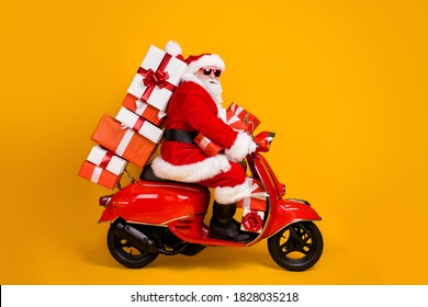 Profile side view of his he nice funny fat white-haired Santa riding moped fast speed hurry up rush carrying bringing pile stack giftbox isolated bright vivid shine vibrant yellow color background