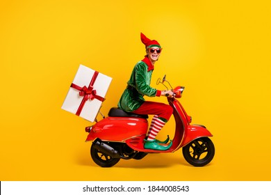 Profile side view of his he nice attractive cheerful funny guy elf riding moped delivering giftbox festal Eve Noel winter fairy isolated over bright vivid shine vibrant yellow color background