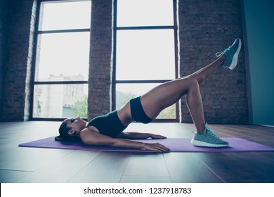 Profile side view of nice charming beautiful enduring strong skinny sportive girl model bodybuilder pilates yoga trainer instructor lifting torso and legs up on mat domestic class work out