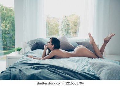 Profile side view photo of adorable good-looking alluring magnificent exquisite brunette lady without underwear lying on bed inside comfort modern bright interior