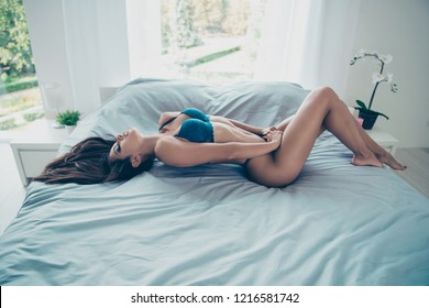 Profile side view photo of beautiful nude delicate winsome lovable fascinating person in blue underwear lying on back in soft bed alone make pleasure comfort light bright room