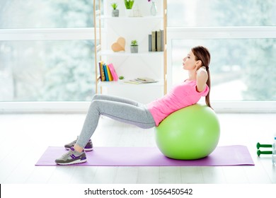 Profile side view photo of concentrated focused aimed purposeful energetic woman using green fit ball for doing crunches wearing tight leggings casual pink tshirt white light studio club gym