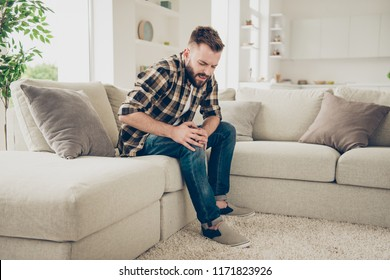 Profile side view photo of frustrated guy with a broken knee in street style checkered shirt sitting on the sofa