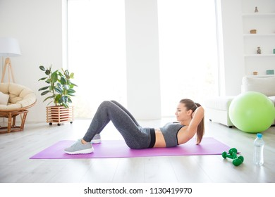 Profile side view photo portrait of charming gorgeous sporty sportive concentrated beautiful with ponytail brunette lady doing crunches on purple carpet at the weekend leading healthy lifestyle